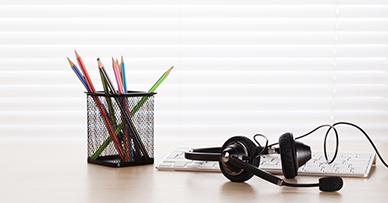 Bureau avec casque d'écoute, un clavier blanc et des crayons de différentes couleurs