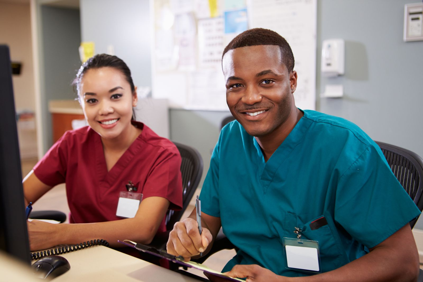 male and female nurse sit at desk