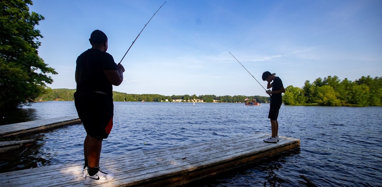 Two camp-goers stand on a floating dock holding fishing rods as they fish in the lake in the background.