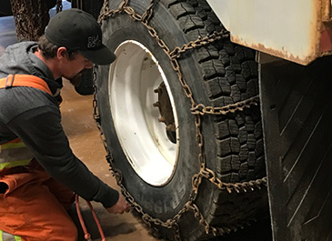 Person putting chains on truck tires