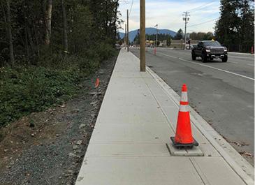 Image of a traffic cone on a new sidewalk