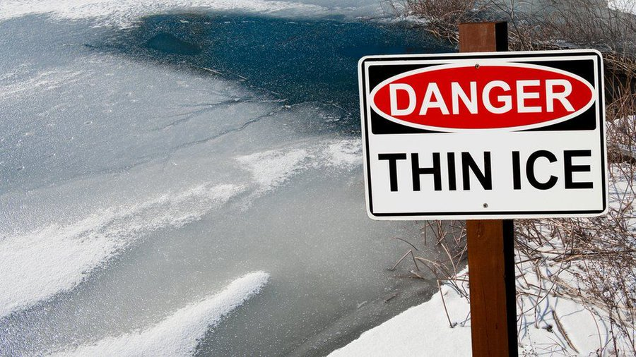 Image of Danger Thin Ice sign near a partially frozen pond