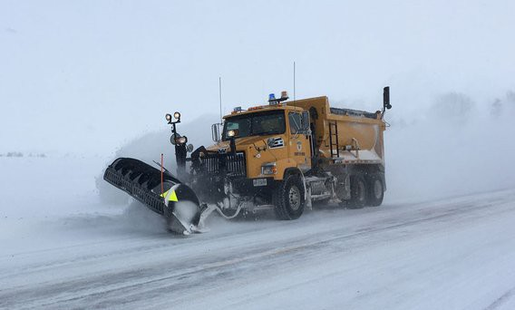 King snow plow that is plowing snow. The snow is